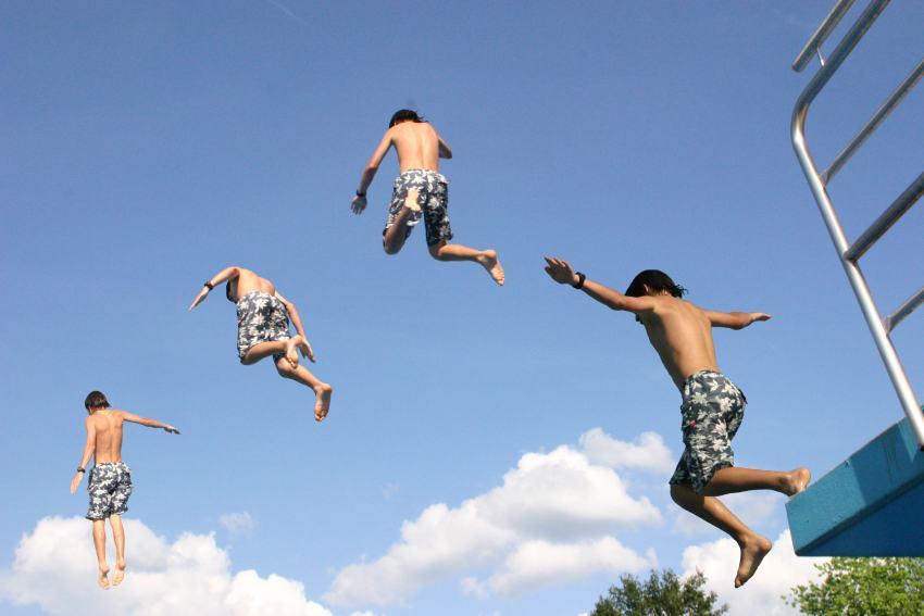 Jungen springen von Klippe ins Wasser