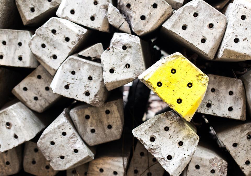 Gelber Betonwürfel unter vielen grauen Würfeln