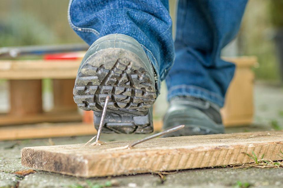 Mann tritt mit Arbeitsschuhen in Nagel