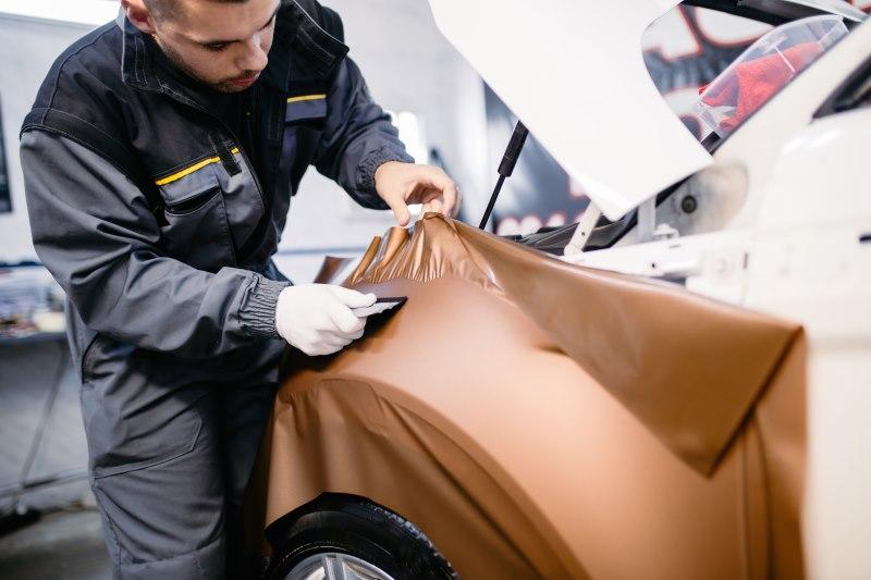 Mann beklebt Auto mit Folie