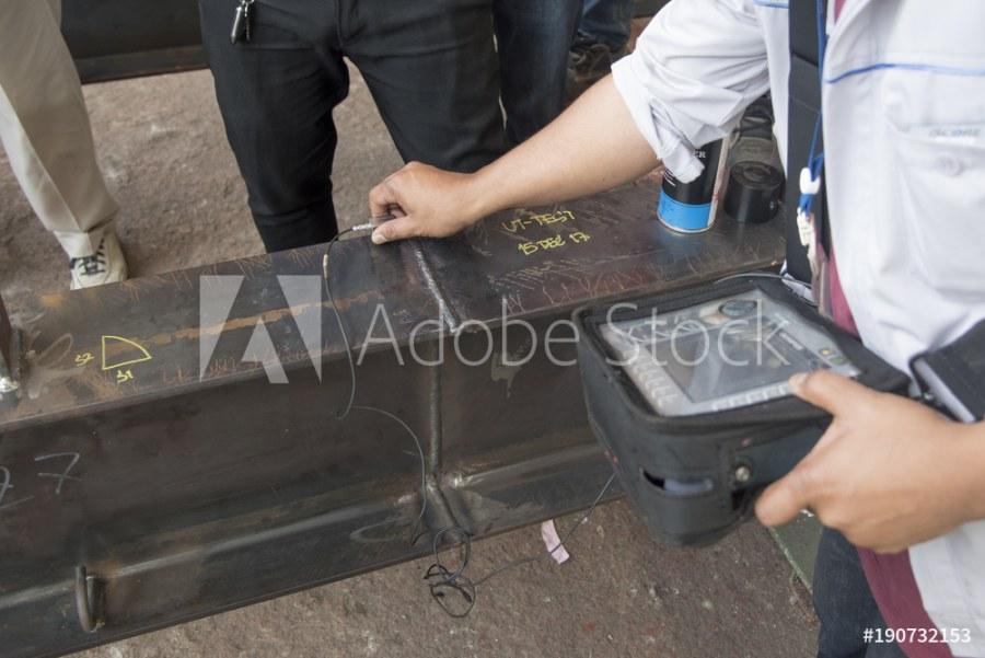 Baustoffprüfer bei der Untersuchung eines Stahlträgers