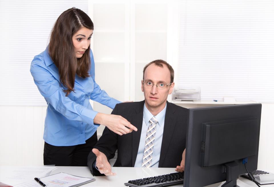 Junge Mitarbeiterin belehrt erfahrenen Kollegen