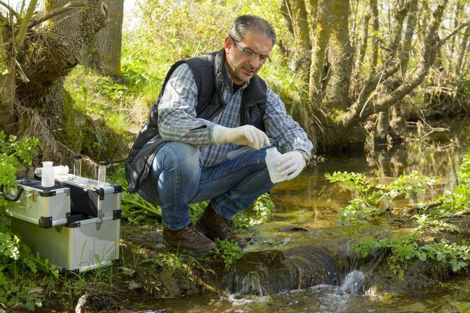 Biologe entnimmt Wasserprobe