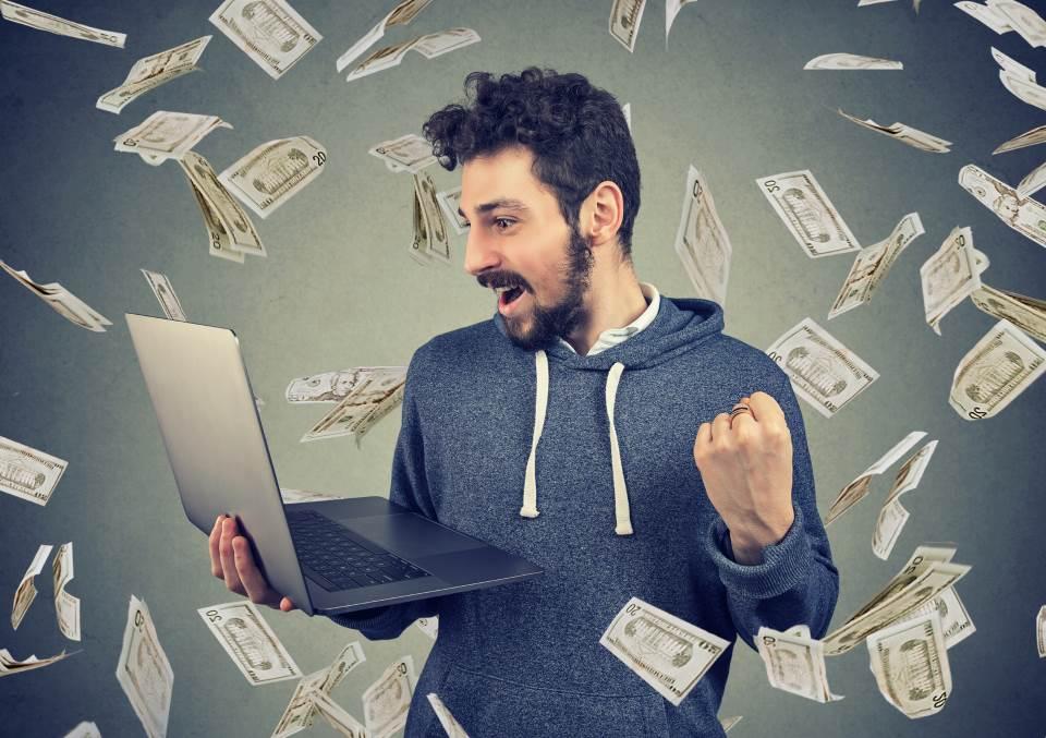 Mann hält Notebook in Hand - Geldscheine fliegen durch Luft