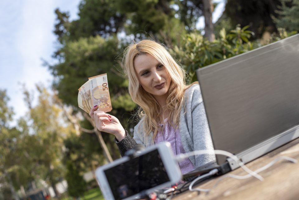 Bloggerin hält Gelscheine in Kamera