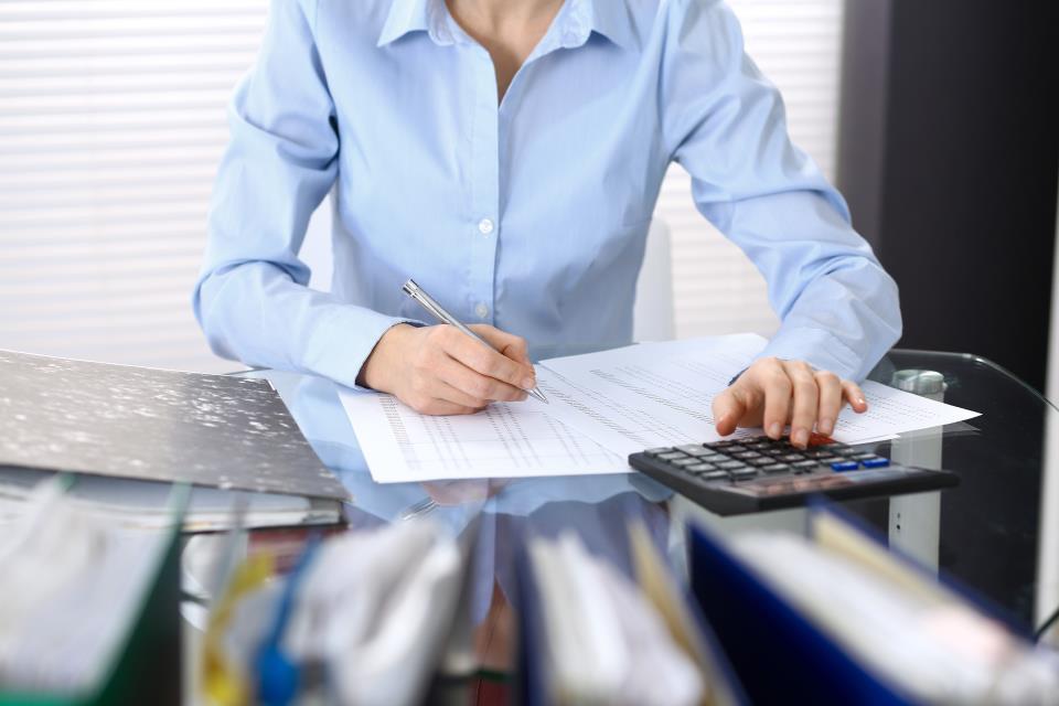 Frau am PC mit Taschenrechner