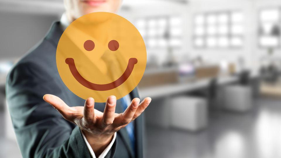 Geschäftsmann mit lachendem Smiley in Hand vor Büro