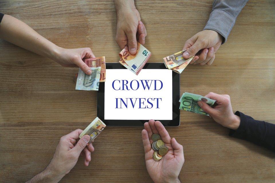 Hände mit Geld auf Schild Crowdinvest
