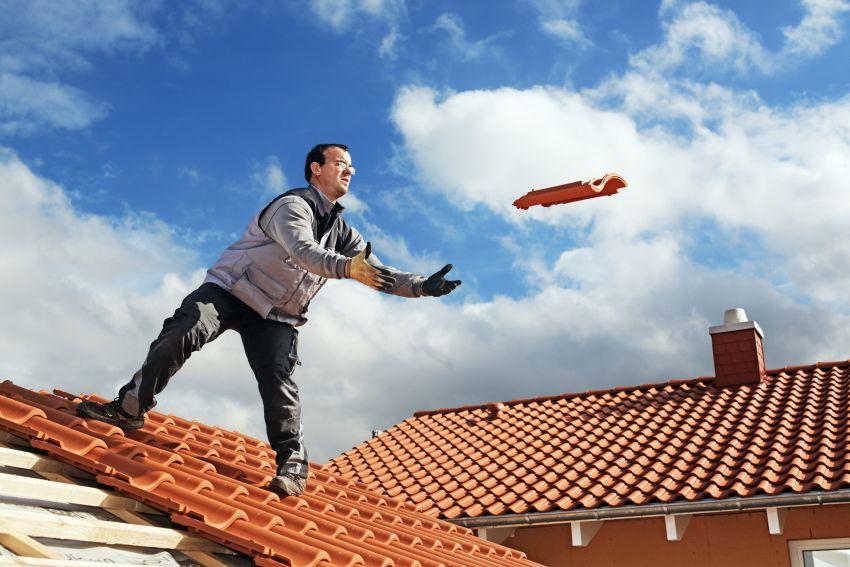 Dachdecker auf Dach wirft Ziegel