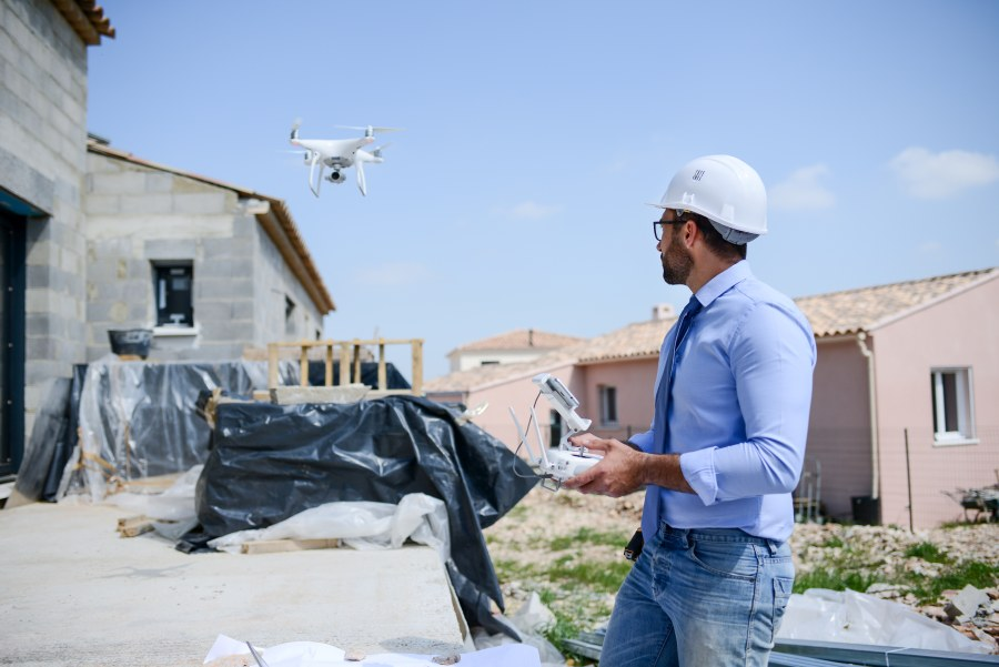 Drohnenpilot steuert Drohne über Neubau