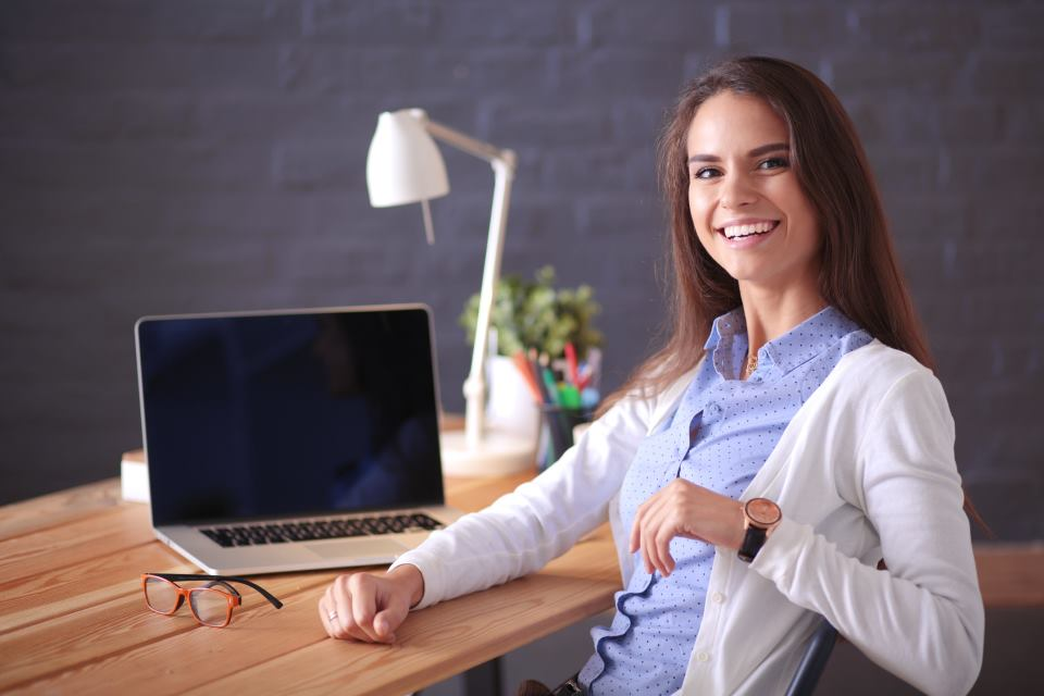 Junge Frau mit E-Business am Notebook