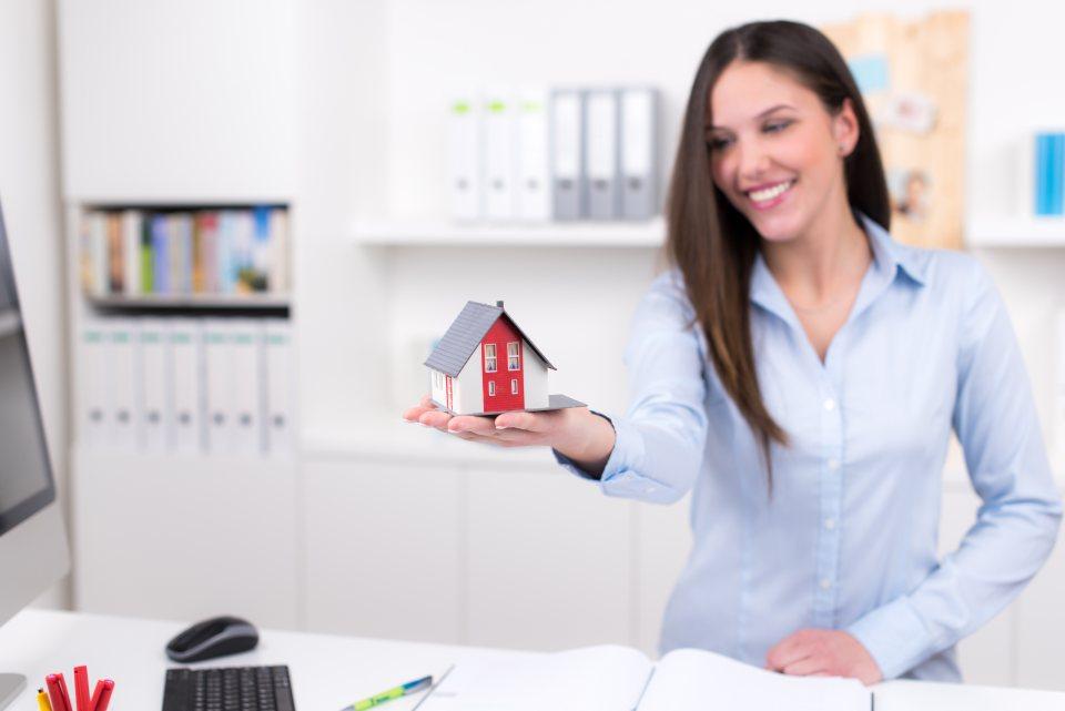 Verkäuferin hat Modellhaus in der Hand