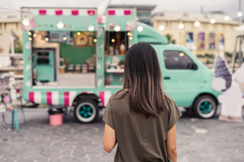 Frau steht vor Food-Truck