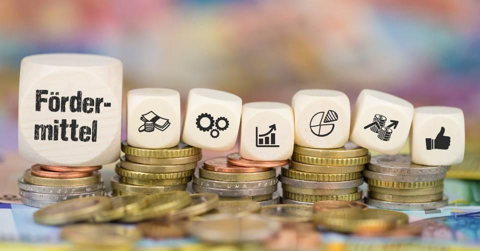 Würfel auf Geld mit Aufschrift Fördermittel