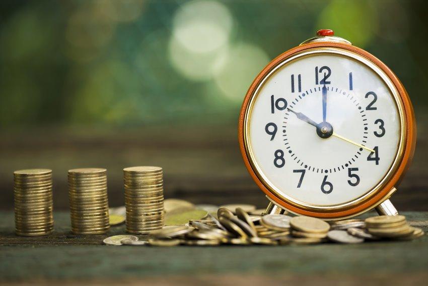 Wecker neben Geldmünzen