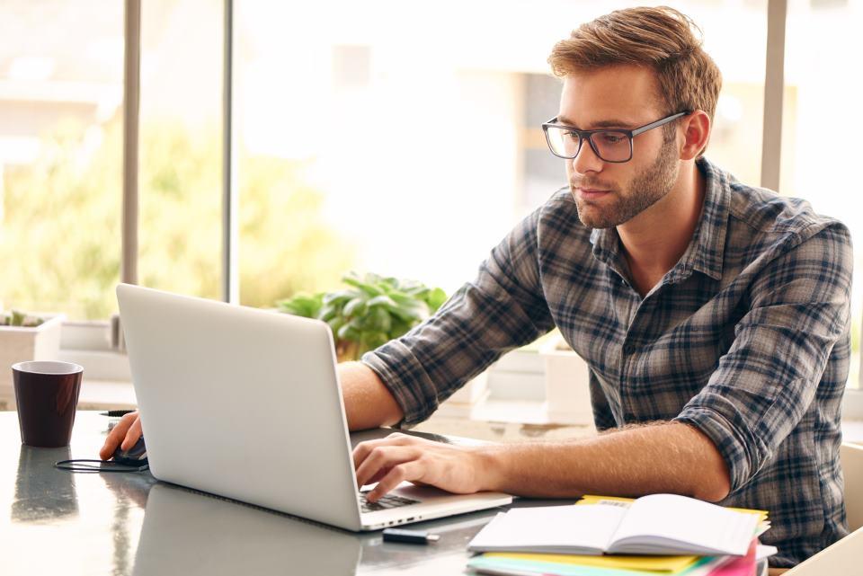 junger Mann am Schreibtisch mit Notebook