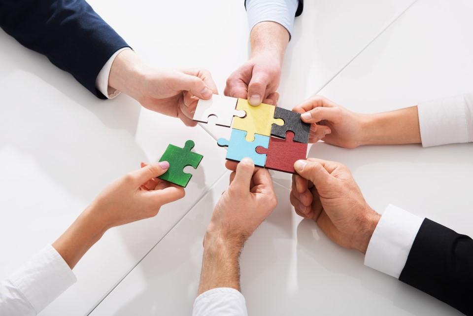 Hände fügen Puzzleteile zusammen