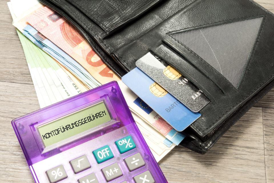 Taschenrechner neben Portemonnaie mit Geldkarten