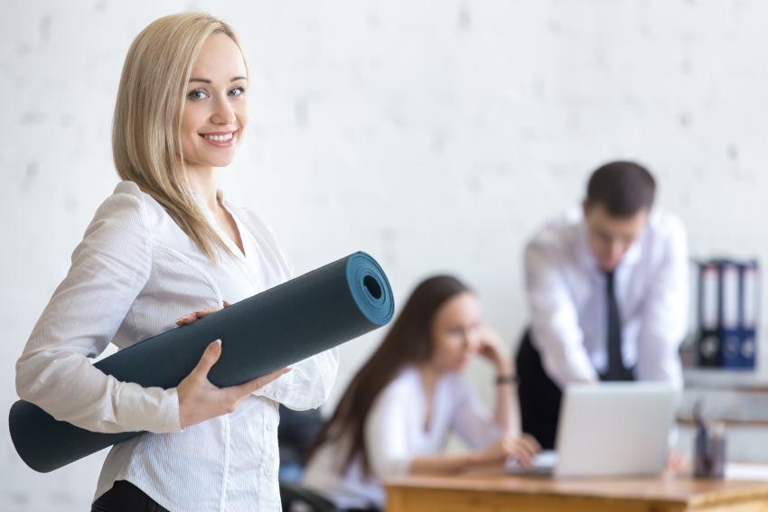 Angestellte mit Fitnessmatte im Büro