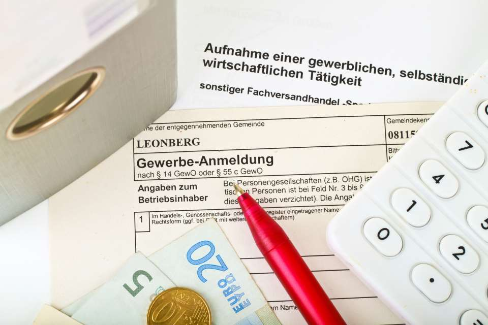 Gewerbeformular mit Geld, Kugelschreiber und Taschenrechner