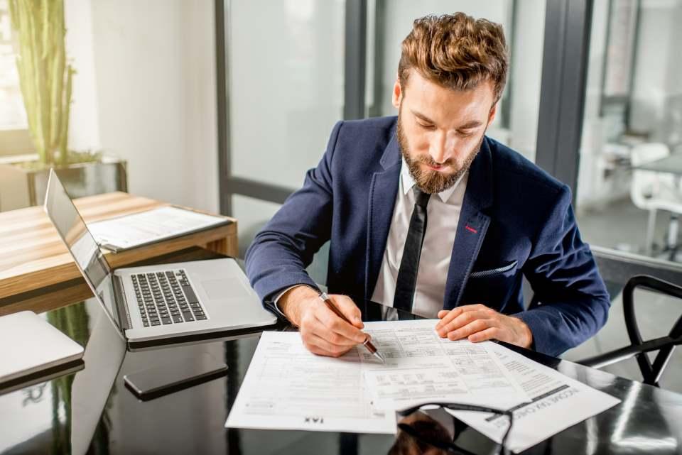 Mann füllt Formular am Schreibtisch aus