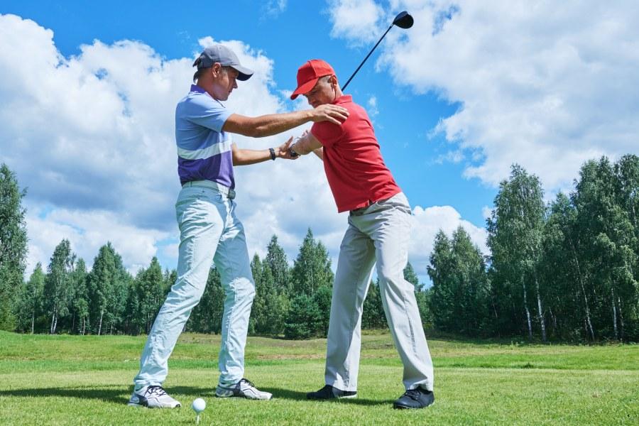 Golflehrer beim Training mit Schüler