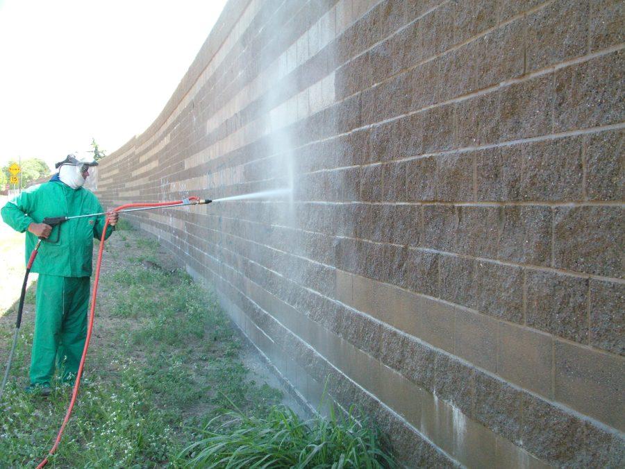 Mann entfernt Graffiti von Mauer