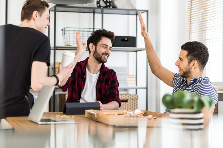 Gründer essen Pizza und klatschen sich ab