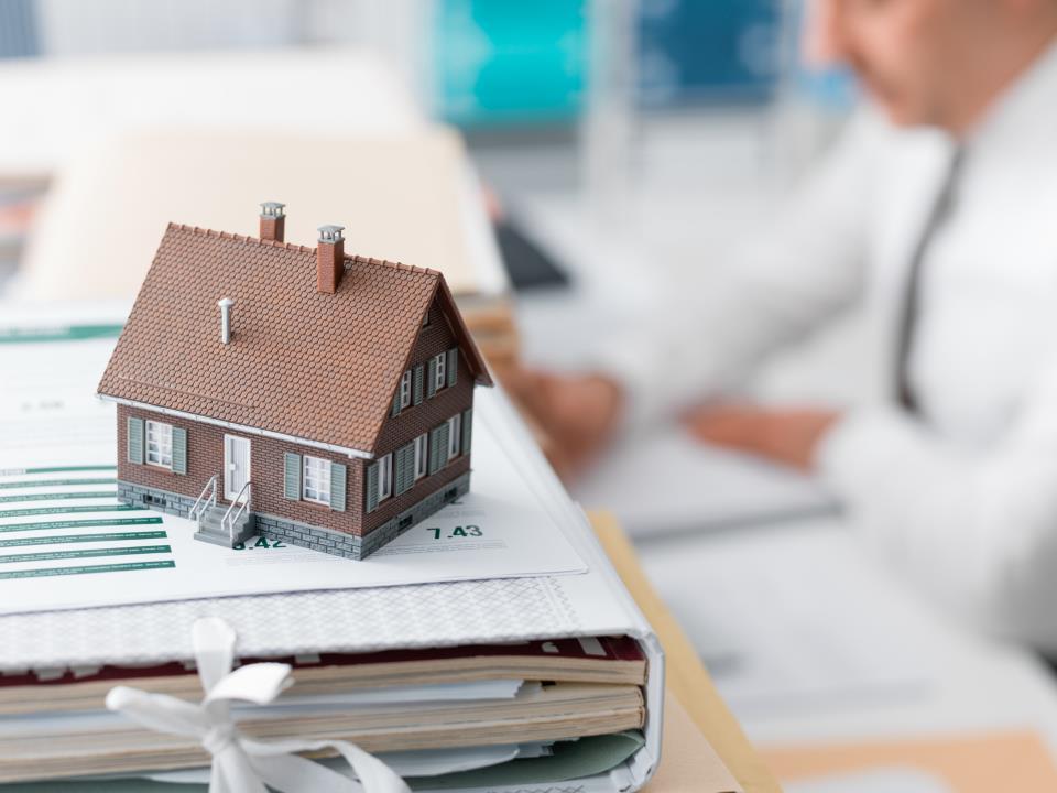 Hausverwalter am Schreibtisch mit Modellhaus