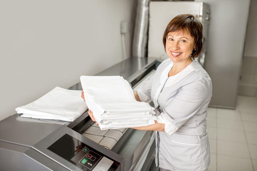 Frau mit gebügelten Handtüchern Heissmangel