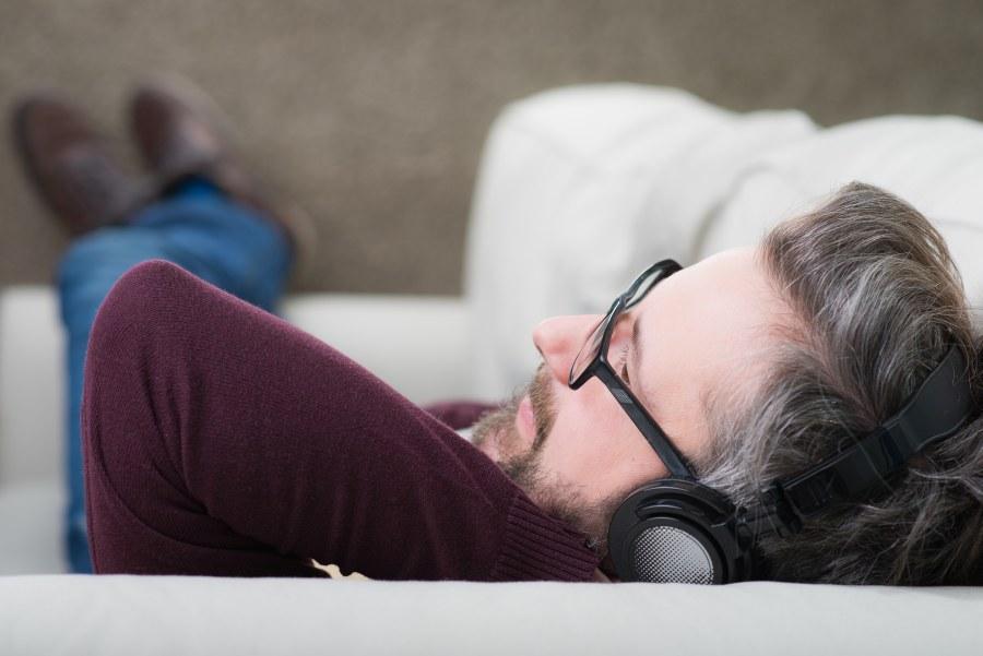 Mann hört Hörbuch auf Couch