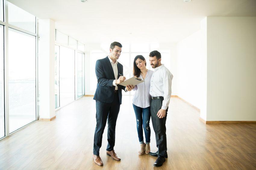 Immobilienmakler bei der Hausbesichtigung mit Ehepaar