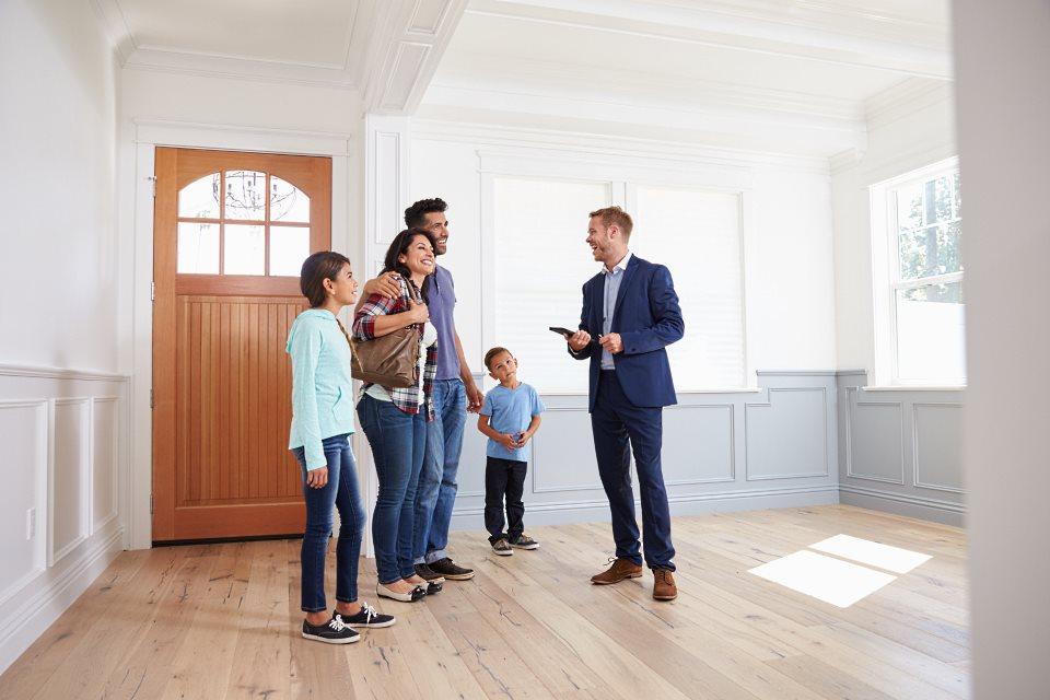 Immobilienmakler bei Besichtigung mit junger Familie