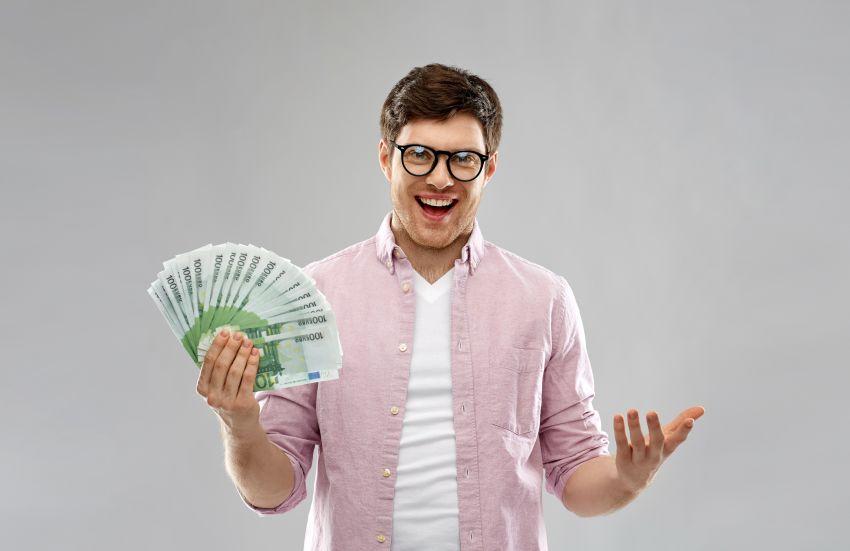 junger Gründer hält Geldscheine in Hand