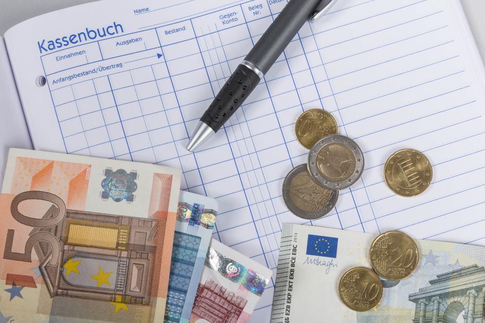 Bargeld liegt auf Kassenbuch