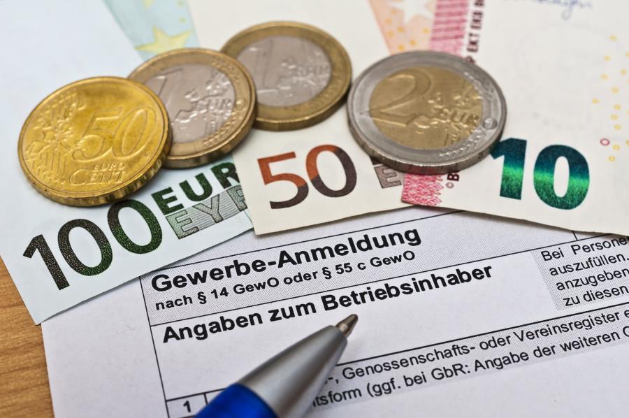 Gewerbeanmeldung Formular mit Geldmünzen