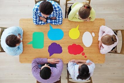 Team am Tisch sitzend mit Konzepten