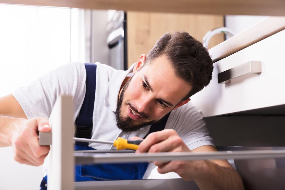 Küchenmonteur schraubt Schublade zusammen