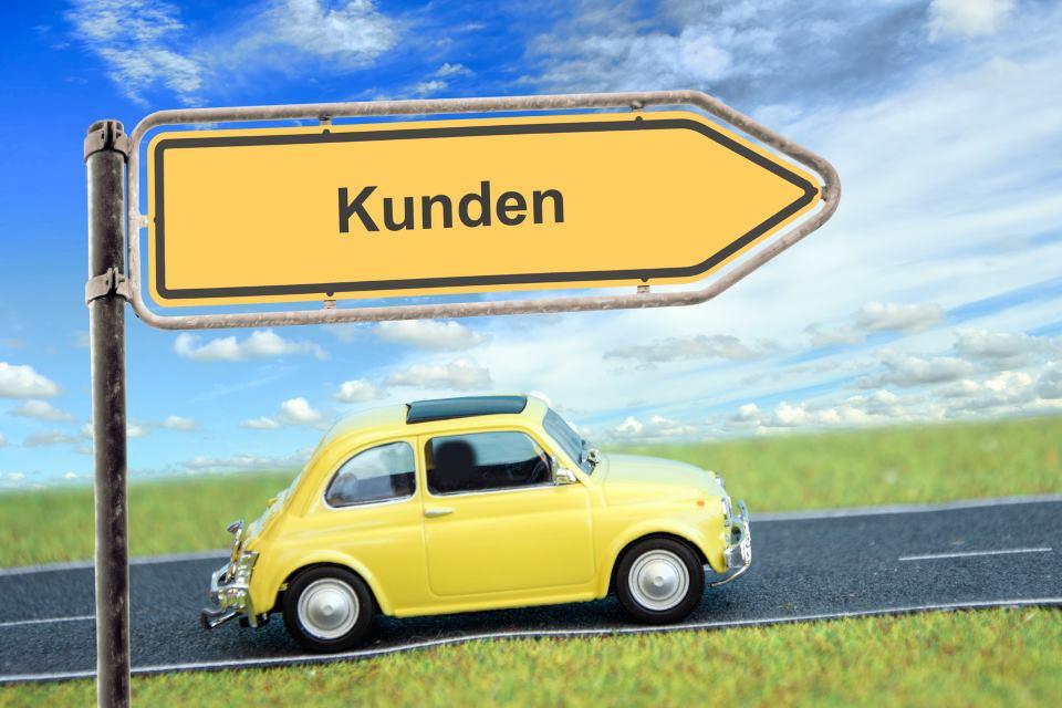 """Gelbes Modellauto fährt an Schild vorbei mit Aufschrift """"Kunden"""""""