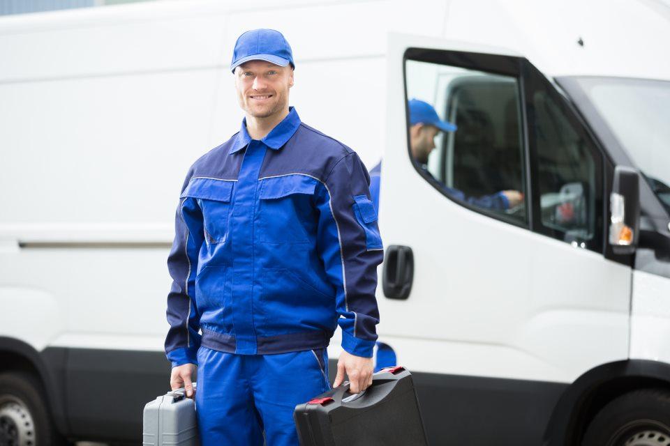 Handwerker mit Koffer vor Lieferwagen