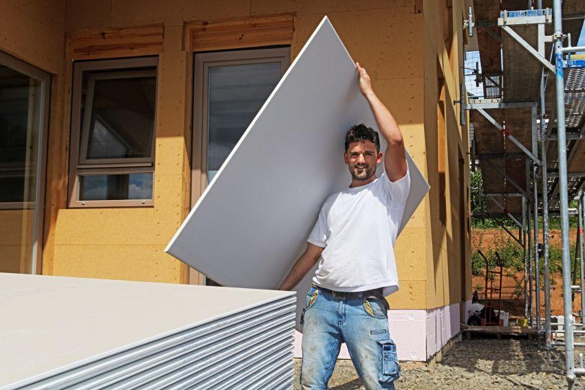 Mann trägt Rigipswand
