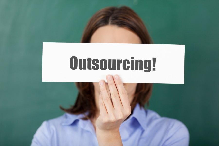 """Frau hält Schild mit """"Outsourcing"""" vor Augen"""