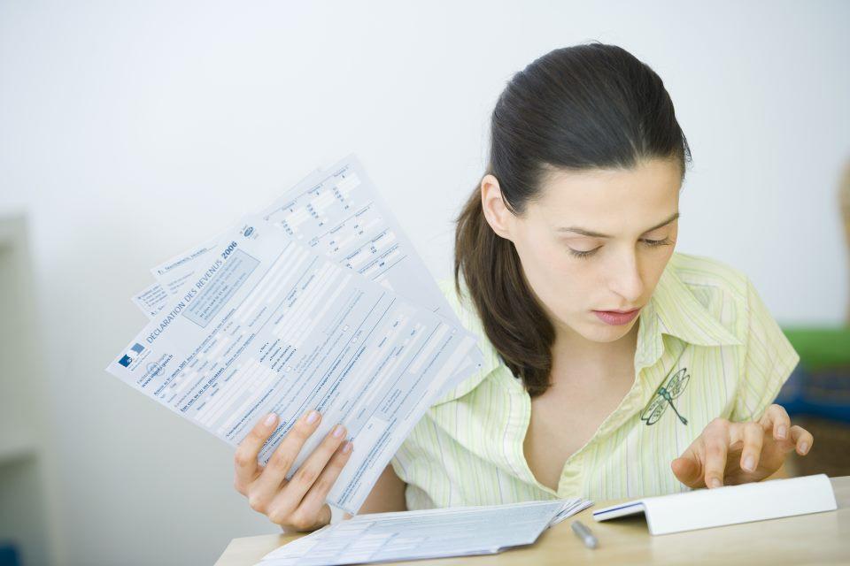 Frau sitzt am Schreibtisch und macht Steuern
