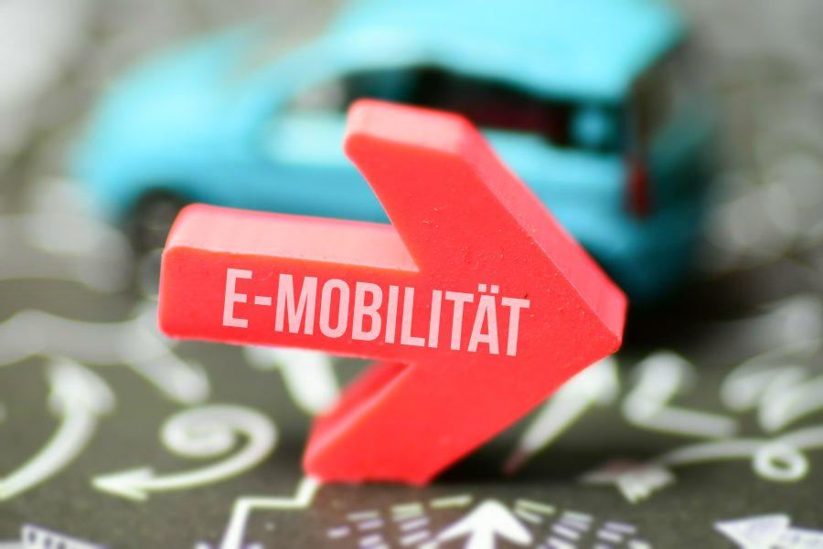 Roter Pfeil mit Aufschrift E-Mobilität vor Auto