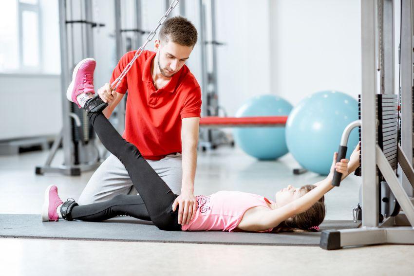 Physiotherapeut streckt Bein von Patientin