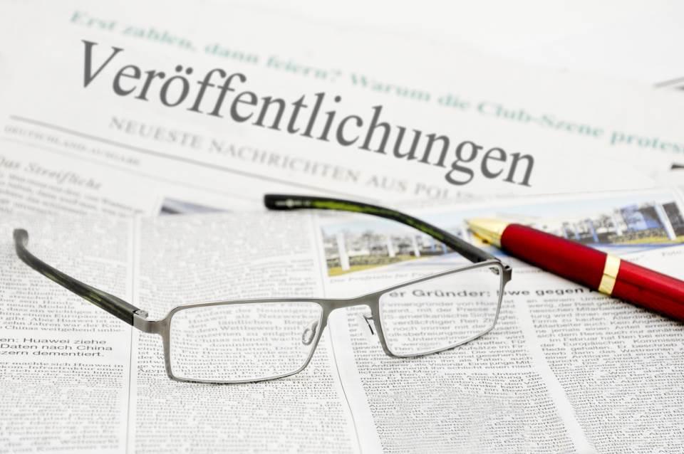 Brille und Stift auf Zeitung