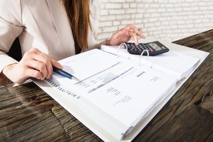 Frau mit Taschenrechner erstellt Rechnung