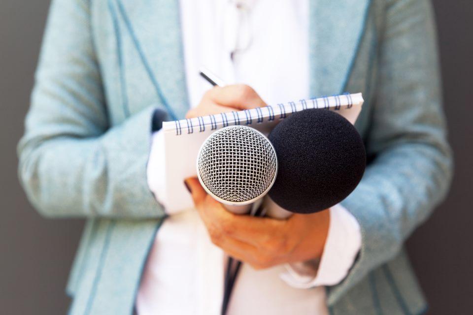 Frau hält Zettel und Mikrofone