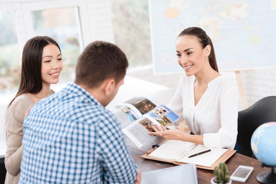 Frau berät Kunden in Reisebüro