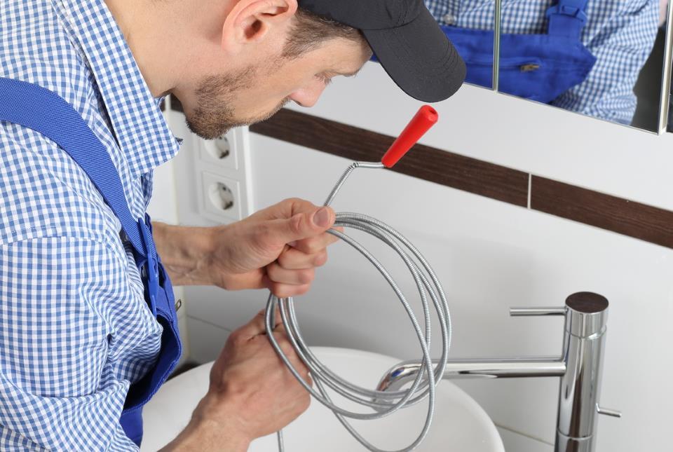 © Klempner führt Spirale in Waschbecken